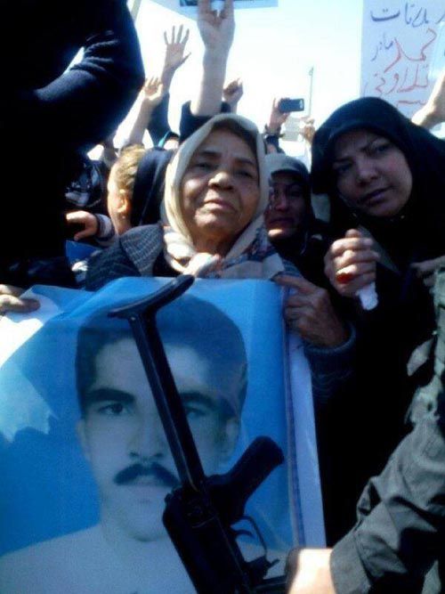 The aged mother holding her son's photo in front of Camp Liberty