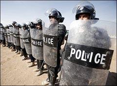 عناصر من شرطه مكافحه الشغب العراقيه يقفون في صف داخل معسكر اشرف .
